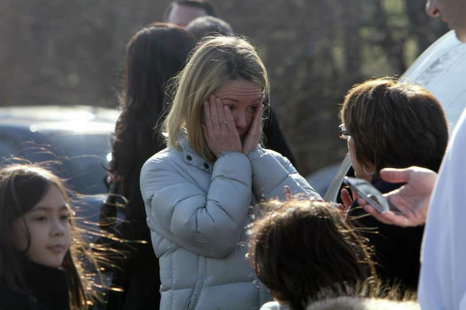 "A woman weeps as she arrives to pick up her children at Sandy Hook Elementary School on Friday after a gunman killed 20 students and eight others. ""We heard lots of gunshots,"" one fourth-grader said. Photo: Frank Becerra Jr., MBO / The Journal News"