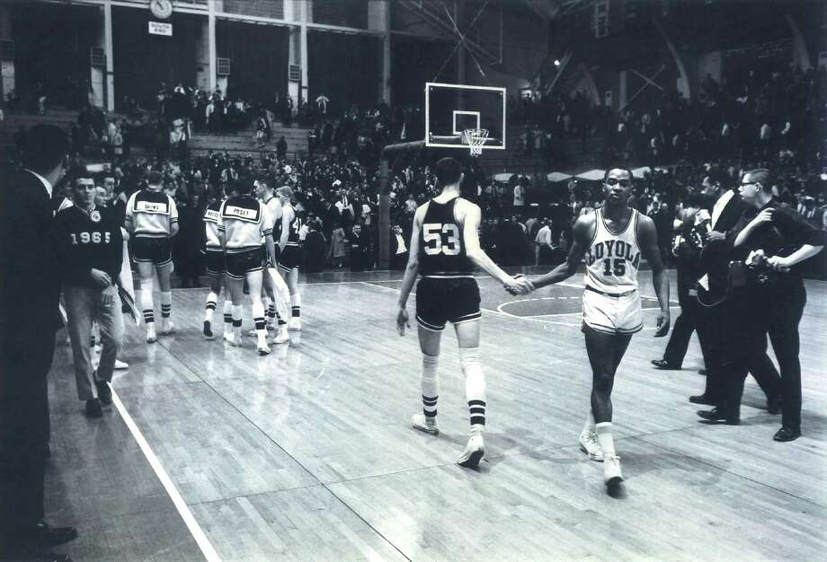 In this photo taken March 15, 1963, and provided by Loyola University Chicago, Mississippi State's Stan Brinker (53) and Loyola's Jerry Harkness (15) shake hands before the NCAA Mideast regional semifinal college basketball game in East Lansing, Mich. Saturday's game between Mississippi State and Loyola in Chicago will be celebrated as a reminder of the landmark contest between the schools that helped alter race relations on the basketball court. (AP Photo/Loyola University Chicago)
