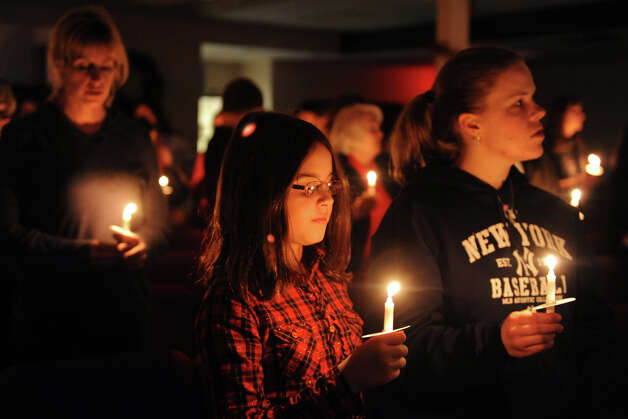 Gabriella Ochoa, left, and Vicki Seppell hold candles during a service at Grace Family Church, in Newtown, Conn. Dec. 14th, 2012. The service was held following the mass shooting at Sandy Hook Elementary School Friday morning. Photo: Ned Gerard / Connecticut Post