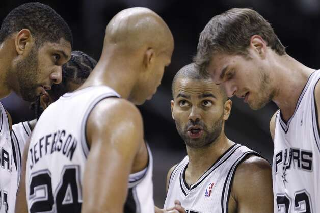 San Antonio Spurs' Tony Parker, center, of France, talks with teammates Richard Jefferson (24), Tim Duncan, left, and Tiago Splitter, right, during a time out in the third quarter of an NBA basketball game against the Portland Trail Blazers, Friday, Jan. 13, 2012, in San Antonio. San Antonio won 99-83. (AP Photo/Eric Gay) (ASSOCIATED PRESS)