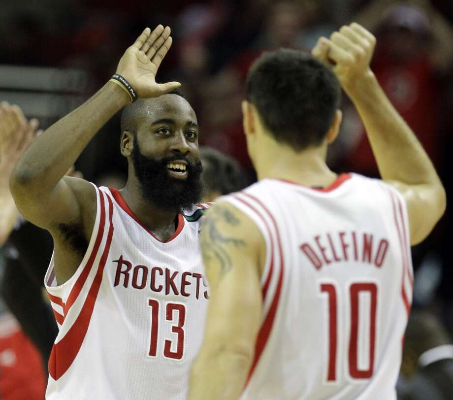 James Harden and Carlos Delfino celebrate a three point shot by teammate Toney Douglas. (Melissa Phillip / Houston Chronicle)