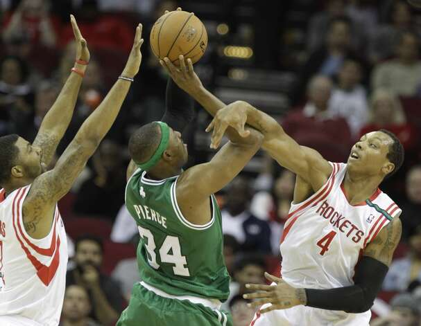 Celtics forward Paul Pierce is fouled as he shoots between Rockets forwards Marcus Morris and Greg Smith during the first half. (Melissa Phillip / Houston Chronicle)
