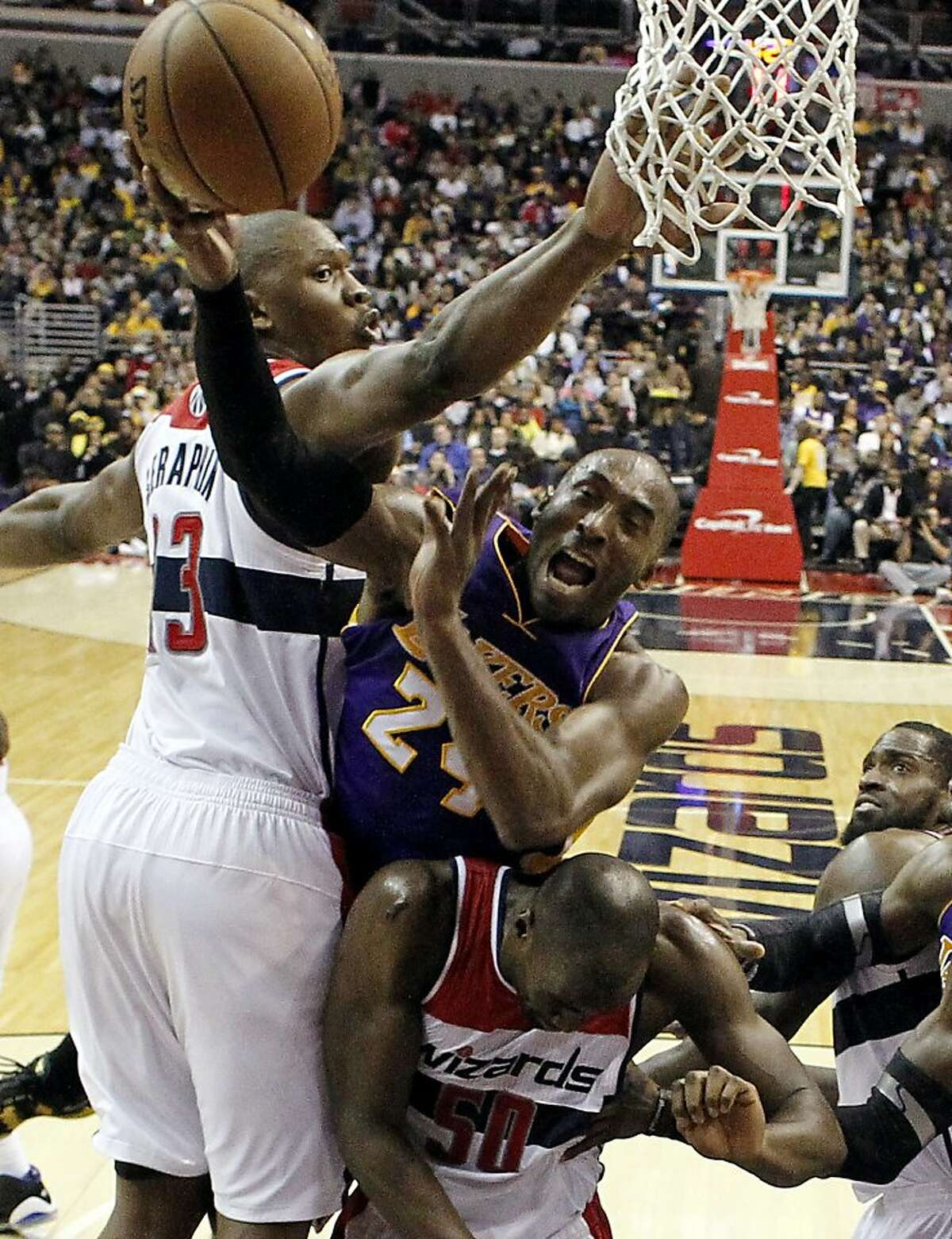 Los Angeles Lakers guard Kobe Bryant is sandwiched between Washington Wizards forward Kevin Seraphin (13) from France, and center Emeka Okafor (50), in the second half of an NBA basketball game Friday, Dec. 14, 2012 in Washington. The Lakers won 102-96. (AP Photo/Alex Brandon)