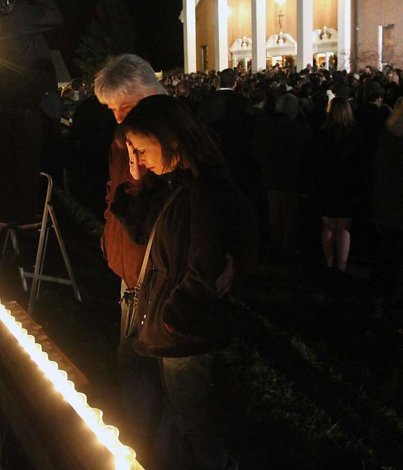 A man and woman pray at a makeshift shrine at a vigil at Saint Rose of Lima church at Saint Rose of Lima church, Friday, Dec. 14, 2012 in Newtown, Conn. A man killed his mother at home and then opened fire Friday inside the elementary school where she taught, massacring 26 people, including 20 children, as youngsters cowered in fear to the sound of gunshots echoing through the building and screams coming over the intercom. (AP Photo/The Journal News, Frank Becerra Jr.)  NYC OUT, NO SALES, ONLINE OUT, TV OUT, NEWSDAY INTERNET OUT; MAGS OUT Photo: Frank Becerra Jr., Associated Press