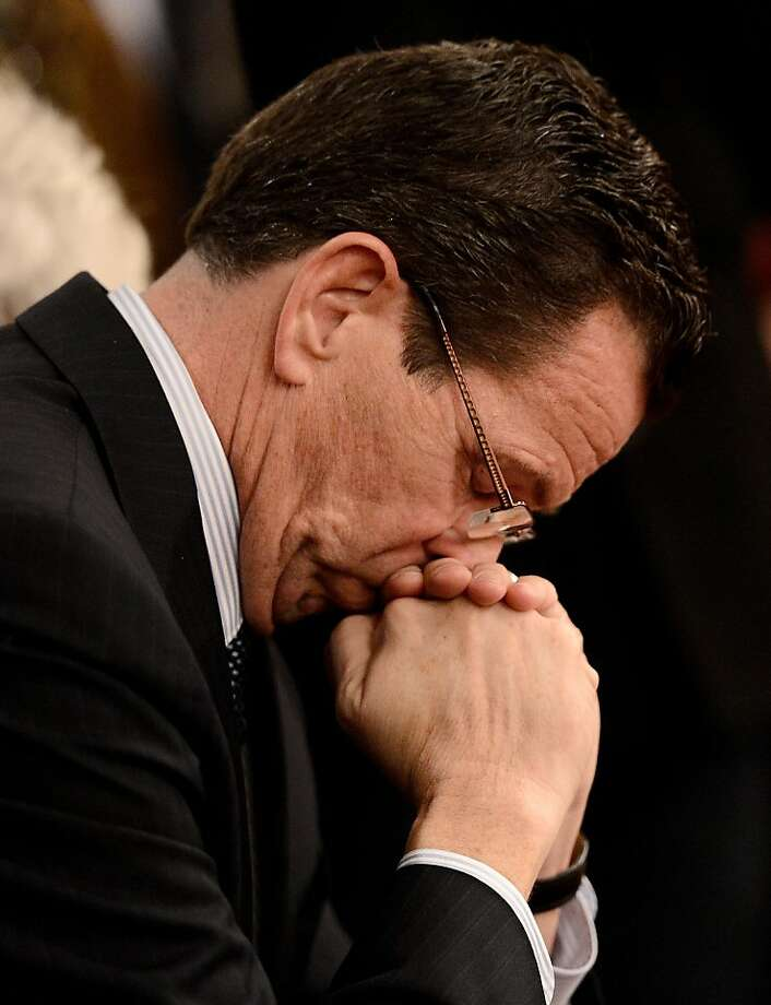 NEWTOWN, CT - DECEMBER 14:  Connecticut Gov. Dan Malloy observes a moment of silence with mourners gathererd inside the St. Rose of Lima Roman Catholic Church at a vigil service for victims of the Sandy Hook School shooting December 14, 2012 in Newtown, Connecticut. Twenty-seven people are dead, including 20 children, after a gunman identified as Adam Lanza in news reports opened fire in the school. Lanza also reportedly died at the scene.  (Photo by Andrew Gombert-Pool/Getty Images) Photo: Pool, Getty Images