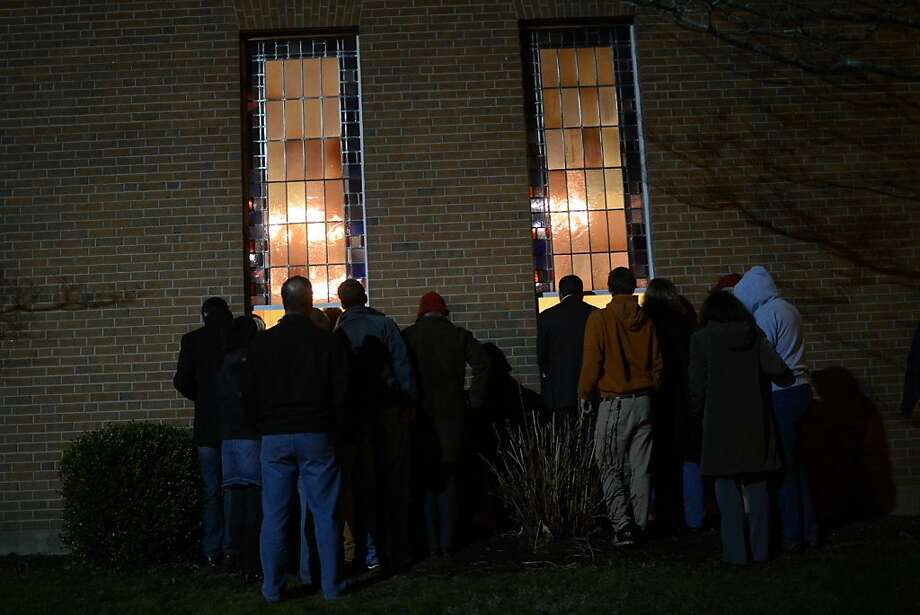 People gather for a prayer vigil at St Rose Church following an elementary school shooting in Newtown, Connecticut, December 14, 2012.  A young gunman slaughtered 20 small children and six teachers on Friday after walking into a school in an idyllic Connecticut town wielding at least two sophisticated firearms.  AFP PHOTO/Emmanuel DUNANDEMMANUEL DUNAND/AFP/Getty Images Photo: Emmanuel Dunand, AFP/Getty Images