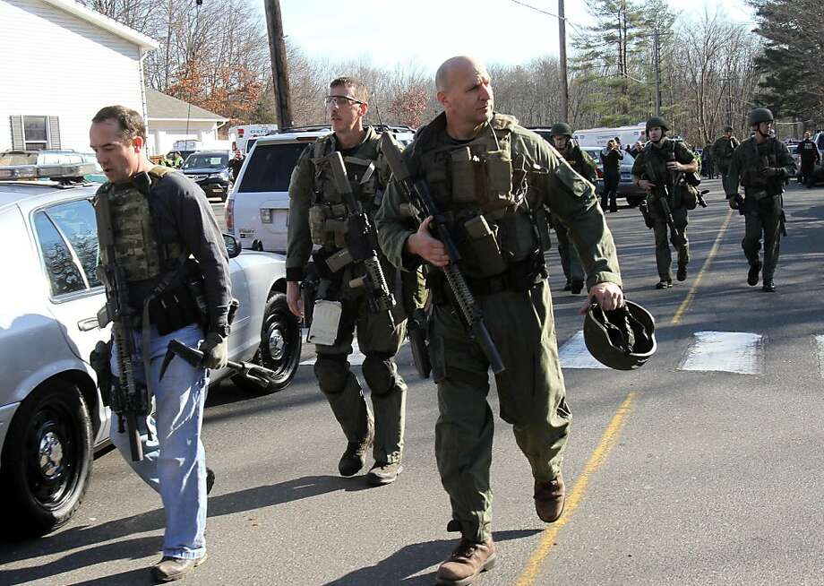Heavily armed Connecticut State troopers are on the scene at the Sandy Hook School in Newtown, Conn. where authorities say a gunman opened fire, leaving 27 people dead, including 20 children, Friday, Dec. 14, 2012.  (AP Photo/The Journal News, Frank Becerra Jr.) MANDATORY CREDIT, NYC OUT, NO SALES, TV OUT, NEWSDAY OUT; MAGS OUT Photo: Frank Becerra Jr., Associated Press