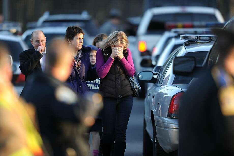 Residents grieve following a shooting December 14, 2012 at Sandy Hook Elementary School on December 14, 2012 in Newtown, Connecticut. At least 26 people, including 20 young children, were killed when a gunman assaulted the school and another body was found dead at a second linked crime scene, police said.  Police spokesman Lieutenant Paul Vance told reporters that the attacker killed 20 children and six adults, including someone that he lived with, at the Sandy Hook Elementary School in Newtown, Connecticut.  The gunman also died at the scene, and a 28th body was found elsewhere.    AFP PHOTO / Don EMMERTDON EMMERT/AFP/Getty Images Photo: Don Emmert, AFP/Getty Images