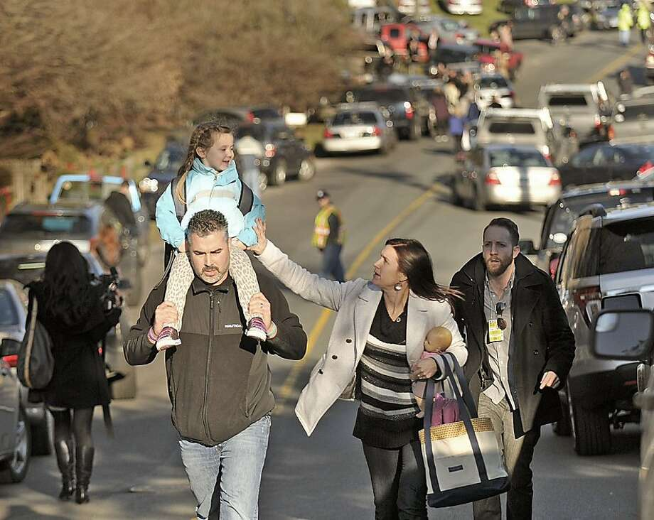 Parents leave Sandy Hook Elementary School in Newtown, Connecticut, with their children Friday, December 14, 2012. Twenty-seven people, including 18 children, have been killed in a shooting at Sandy Hook Elementary School. (John Woike/Hartford Courant/MCT) Photo: John Woike, McClatchy-Tribune News Service
