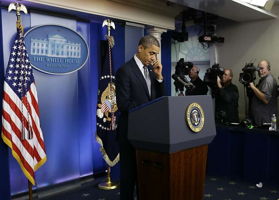 President Barack Obama wipes his eye as he speaks about the school shooting in Newtown, Conn., Friday, Dec. 14, 2012, in the briefing room of the White House in Washington. (AP Photo/Charles Dharapak) Photo: Charles Dharapak, Associated Press
