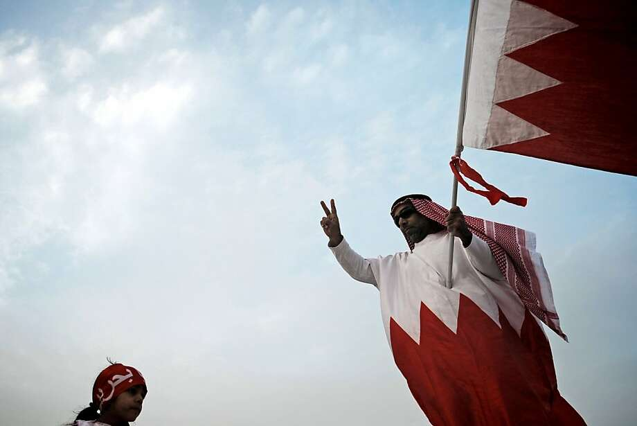 A Bahraini Shiite Muslim protester waves the national flag during an anti-government demonstration in the village of Jannusan, west of Manama, on December 14, 2012. Thousands of supporters of Bahrain's largely Shiite Muslim opposition demonstrated peacefully near Manama, calling for democratic reform in the turbulent Sunni-ruled Gulf country, witnesses said. Photo: Mohammed Al-shaikh, AFP/Getty Images