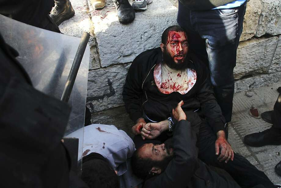 Injured men take shelter during clashes between supporters and opponents of President Mohammed Morsi in Alexandria, Egypt, Friday, Dec. 14, 2012, a day before the referendum on the constitution.  Opposing sides in Egypt's political crisis were staging rival rallies on Friday, the final day before voting starts on a contentious draft constitution that has plunged the country into turmoil and deeply divided the nation. Photo: Ahmed Ramadan, Associated Press
