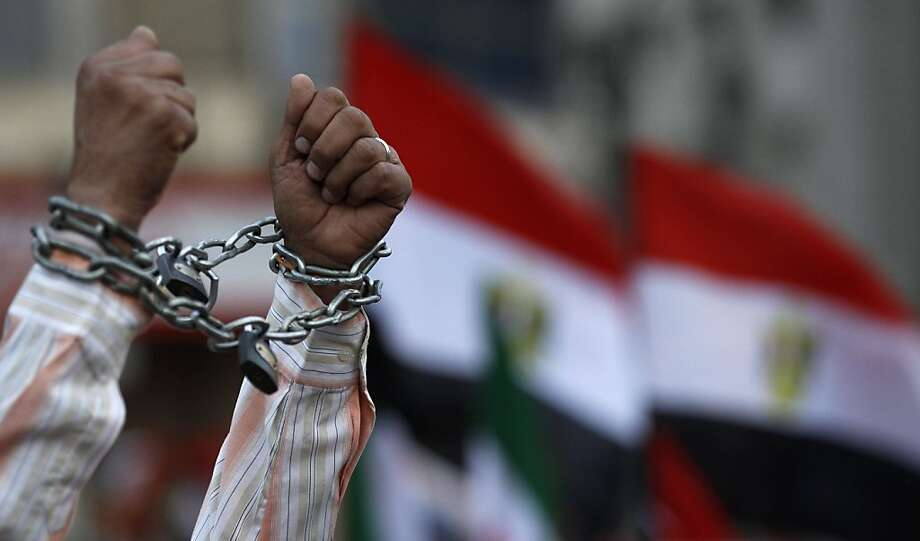 A protester shows his chained hands during a demonstration against a constitution drafted by Islamist supporters of President Mohammed Morsi in Tahrir square in Cairo, Egypt, Friday, Dec. 14, 2012. Opposing sides in Egypt's political crisis were staging rival rallies on Friday, the final day before voting starts on a contentious draft constitution that has plunged the country into turmoil and deeply divided the nation. Photo: Petr David Josek, Associated Press