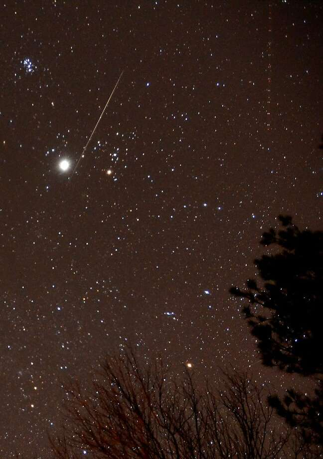 A meteor is shown by Jupiter as an aircraft passes at upper right during the annual Geminid meteor shower over Springville, Ala., Thursday, night Dec. 13, 2012. Photo: Mark Almond, Associated Press