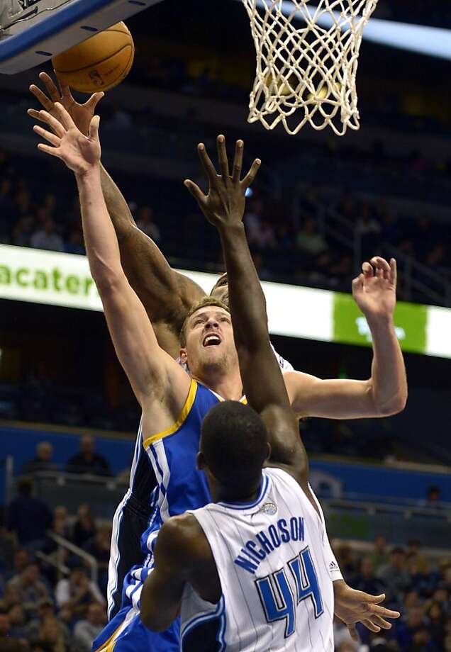 Golden State Warriors forward David Lee, center, puts up a shot between Orlando Magic forward Andrew Nicholson (44) and Glen Davis during the first half of an NBA basketball game in Orlando, Fla., Friday, Dec. 14, 2012. (AP Photo/Phelan M. Ebenhack) Photo: Phelan M. Ebenhack, Associated Press