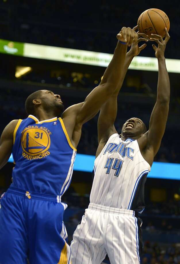 Orlando Magic forward Andrew Nicholson (44) grabs a rebound over Golden State Warriors forward Festus Ezeli during the first half of an NBA basketball game in Orlando, Fla., Friday, Dec. 14, 2012.(AP Photo/Phelan M. Ebenhack) Photo: Phelan M. Ebenhack, Associated Press