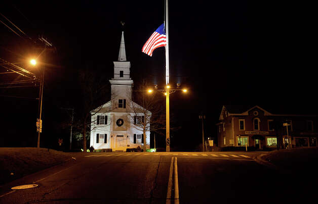 A U.S. flag flies at half-staff on Main Street in honor of the people killed when a gunman opened fire inside a Connecticut elementary school, Saturday, Dec. 15, 2012, in Newtown, Conn. Photo: AP