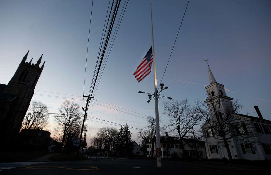An American flag flies at half-staff as dawn breaks, Saturday, Dec. 15, 2012 in Newtown, Conn.  A gu