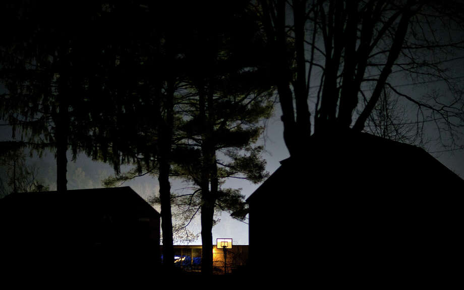 A basketball hoop is seen behind the Sandy Hook Elementary School as police flood lights light up the sky, Saturday, Dec. 15, 2012, in Sandy Hook, Conn. A gunman killed his mother at their home and later walked into Sandy Hook Elementary School Friday and opened fire, killing 26 people, including 20 children. Photo: AP
