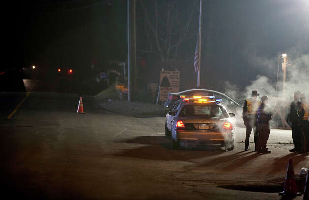 A Connecticut State Troopers stand guard at the entrance to the Sandy Hook Elementary School, Saturday, Dec. 15, 2012, in Newtown, Conn. A gunman killed his mother at their home and later walked into Sandy Hook Elementary School Friday and opened fire, killing 26 people, including 20 children. Photo: AP
