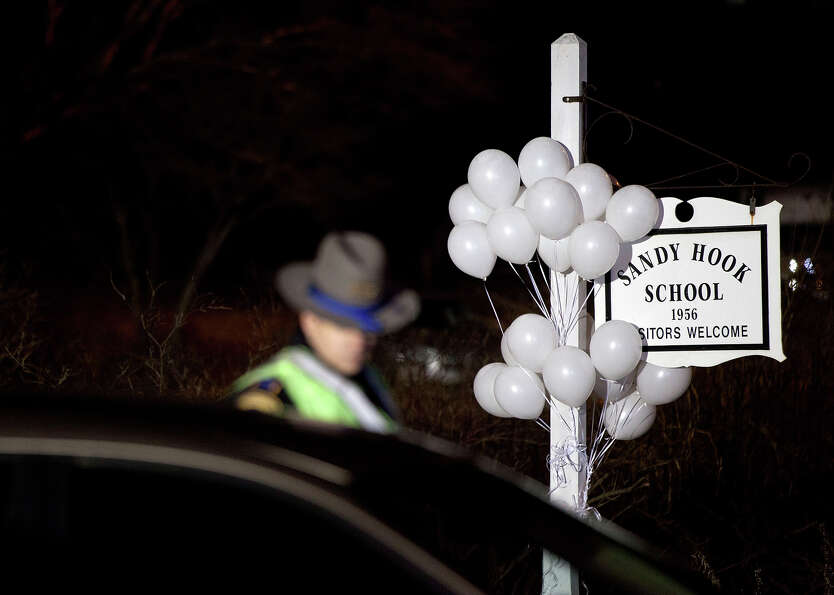 White balloons decorate the sign for the Sandy Hook Elementary School as a Connecticut State Trooper