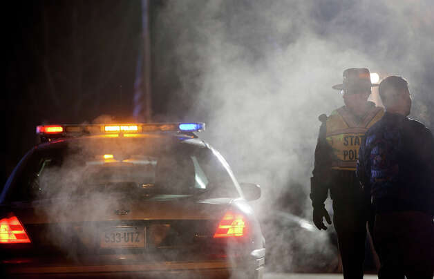 A Connecticut State Trooper stands guard at the entrance to the Sandy Hook Elementary School, Saturday, Dec. 15, 2012, in Newtown, Conn. A gunman killed his mother at their home and later walked into Sandy Hook Elementary School Friday and opened fire, killing 26 people, including 20 children. Photo: AP