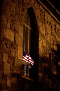 A U.S. flag is reflected in a church window while flying at half-staff on Main Street in honor of the people killed when a gunman opened fire inside a Connecticut elementary school, Saturday, Dec. 15, 2012, in Newtown, Conn. Photo: AP