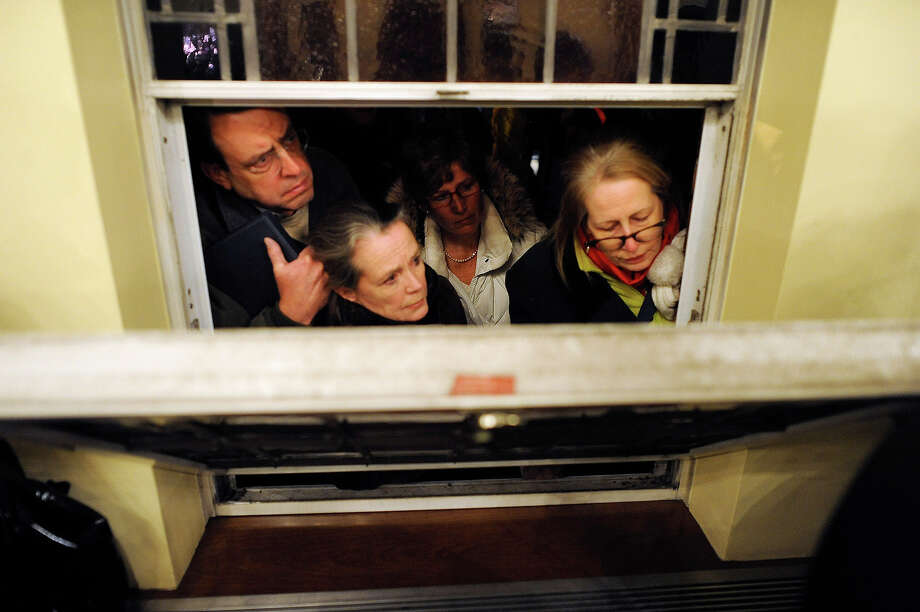 Mourners look in from outside during a vigil service for victims of the Sandy Hook Elementary School shooting, at the St. Rose of Lima Roman Catholic Church in Newtown, Conn. Friday, Dec. 14, 2012. A man killed his mother at their home and then opened fire Friday inside the elementary school where she taught, massacring 26 people, including 20 children, as youngsters cowered in fear to the sound of gunshots reverberating through the building and screams echoing over the intercom Photo: AP