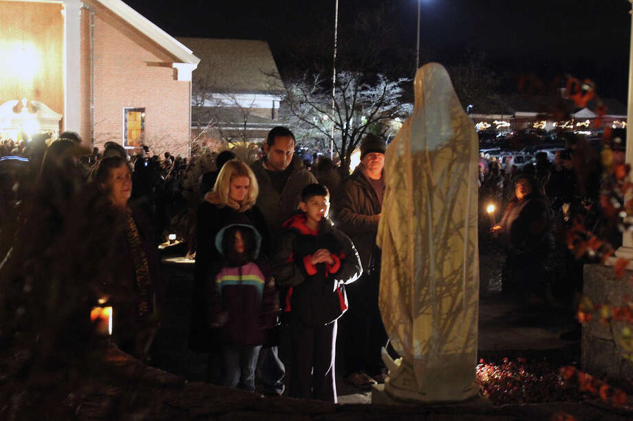 A family prays at a statue of the Virgin Mary outside Saint Rose of Lima church,  Friday, Dec. 14, 2012 in Newtown, Conn. A man killed his mother at home and then opened fire Friday inside the elementary school where she taught, massacring 26 people, including 20 children, as youngsters cowered in fear to the sound of gunshots echoing through the building and screams coming over the intercom. (AP Photo/The Journal News, Frank Becerra Jr.)  NYC OUT, NO SALES, ONLINE OUT, TV OUT, NEWSDAY INTERNET OUT; MAGS OUT Photo: AP