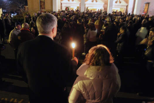 Thousands of people attend vigil at Saint Rose of Lima church at Saint Rose of Lima church, Friday, Dec. 14, 2012 in Newtown, Conn. A man killed his mother at home and then opened fire Friday inside the elementary school where she taught, massacring 26 people, including 20 children, as youngsters cowered in fear to the sound of gunshots echoing through the building and screams coming over the intercom. (AP Photo/The Journal News, Frank Becerra Jr.)  NYC OUT, NO SALES, ONLINE OUT, TV OUT, NEWSDAY INTERNET OUT; MAGS OUT Photo: AP