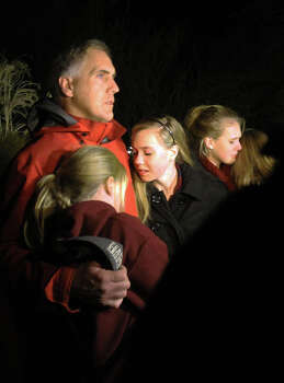 A man hugs his young daughters as they attend a vigil at Saint Rose of Lima church at Saint Rose of Lima church, Friday, Dec. 14, 2012 in Newtown, Conn. A man killed his mother at home and then opened fire Friday inside the elementary school where she taught, massacring 26 people, including 20 children, as youngsters cowered in fear to the sound of gunshots echoing through the building and screams coming over the intercom. (AP Photo/The Journal News, Frank Becerra Jr.)  NYC OUT, NO SALES, ONLINE OUT, TV OUT, NEWSDAY INTERNET OUT; MAGS OUT Photo: AP