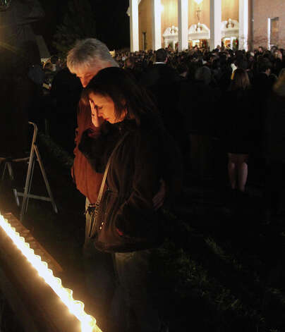 A man and woman pray at a makeshift shrine at a vigil at Saint Rose of Lima church at Saint Rose of Lima church, Friday, Dec. 14, 2012 in Newtown, Conn. A man killed his mother at home and then opened fire Friday inside the elementary school where she taught, massacring 26 people, including 20 children, as youngsters cowered in fear to the sound of gunshots echoing through the building and screams coming over the intercom. (AP Photo/The Journal News, Frank Becerra Jr.)  NYC OUT, NO SALES, ONLINE OUT, TV OUT, NEWSDAY INTERNET OUT; MAGS OUT Photo: AP
