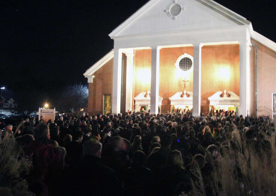 Thousands attend a vigil for the victims of the school shooting at Saint Rose of Lima church, Friday, Dec. 14, 2012 in Newtown, Conn. A man killed his mother at home and then opened fire Friday inside the elementary school where she taught, massacring 26 people, including 20 children, as youngsters cowered in fear to the sound of gunshots echoing through the building and screams coming over the intercom. Photo: AP