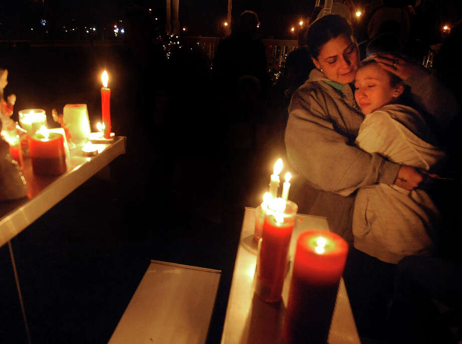 Brenda Hernadez of Enfield Conn., comforts her daughter Crystal at a makeshift shrine on the Enfield Town Green, Friday evening, December 14, 2012,  after a candlelight vigil in Enfield, Conn.  The vigil was organized by social media in memory of the school shooting victims in Newtown as residents in Enfield, 70 miles from Newtown, and in through out the state, feel the grief of the mass shooting at the Sandy Hook Elementary School Friday morning. (AP Photo/Journal Inquirer, Jim Michaud) MANDATORY CREDIT Photo: AP