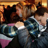 Girls embraces outside St. Rose of Lima Roman Catholic Church, which was filled to capacity, during a healing service held in for victims of an elementary school shooting in Newtown, Conn., Friday, Dec. 14, 2012. A gunman opened fire at Sandy Hook Elementary School in Newtown, killing 26 people, including 20 children.