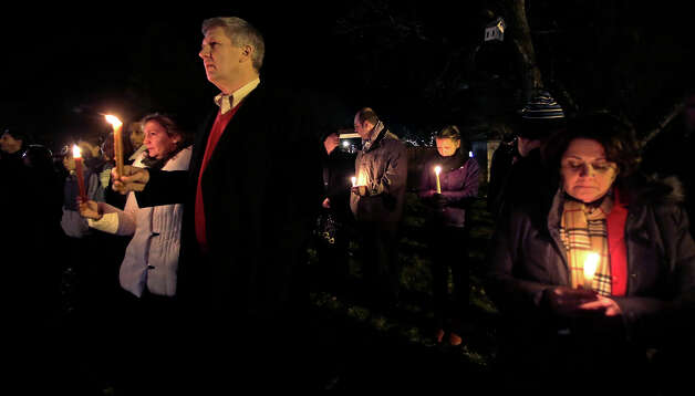 Men and women hold candles in vigil outside St. Rose of Lima Roman Catholic Church during a healing service held in for victims of an elementary school shooting in Newtown, Conn., Friday, Dec. 14, 2012.  A gunman opened fire at Sandy Hook Elementary School in the town, killing 26 people, including 20 children. Photo: AP