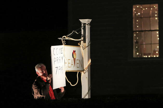 Ray Ruzek hangs a sign inviting people to a prayer meeting at the Heaven Ice Cream shop, Friday, Dec. 14, 2012 in Newtown, Conn. A gunman walked into the school Friday and opened fire, killing 26 people, including 20 children. Photo: AP