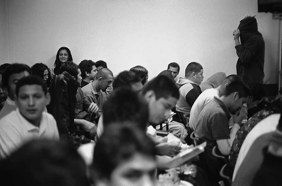 People deported from the United States back to El Salvador crowd inot a room in El Salvador. Photo: Juan Carlos