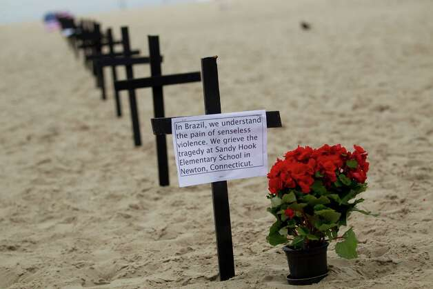 Crosses are set at the Copacabana Beach in Rio de Janeiro, Saturday, Dec. 15, 2012, in memory of the school shooting victims in Newtown, Conn. Photo: Silvia Izquierdo