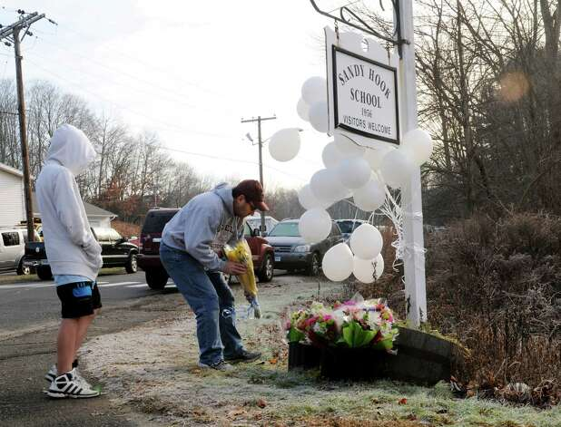 A sympathetic man accompanied by a young boy came to place flowers next to the Sandy Hook Elementary School sign in newtown , Conn. on Saturday morning Dec. 15, 2012. Twenty children and six adults were killed by a gunman yesterday at the school. Photo: Will Waldron, Hearst Connecticut Newspapers/Wi / The News-Times