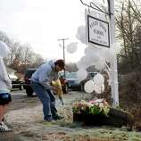 A sympathetic man accompanied by a young boy came to place flowers next to the Sandy Hook Elementary School sign in newtown , Conn. on Saturday morning Dec. 15, 2012. Twenty children and six adults were killed by a gunman yesterday at the school.