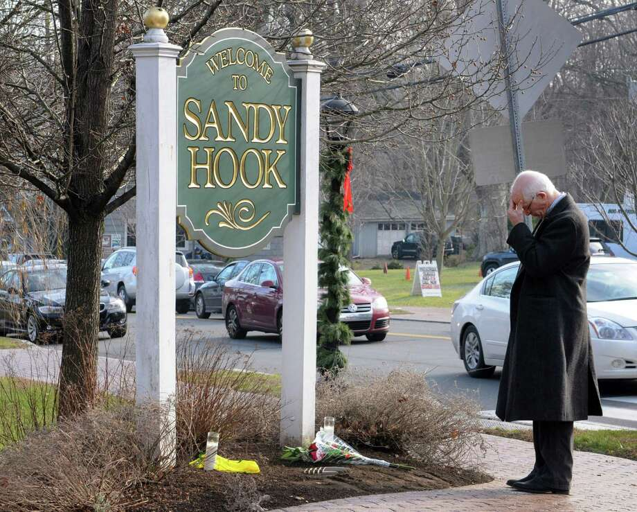 Dr. Steve Wruble, a trauma psychiatrist from NJ reflected on yesterdayâÄôs tragedy at Sandy Hook Elementary School after placing flowers by a sign in Newtown Conn., Saturday morning Dec. 15, 2012. Twenty-seven people including 20 children were killed by a lone gunman yesterday at the school. Photo: Will Waldron, Hearst Connecticut Newspapers/Wi / The News-Times