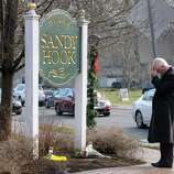 Dr. Steve Wruble, a trauma psychiatrist from NJ reflected on yesterdayâÄôs tragedy at Sandy Hook Elementary School after placing flowers by a sign in Newtown Conn., Saturday morning Dec. 15, 2012. Twenty-seven people including 20 children were killed by a lone gunman yesterday at the school.