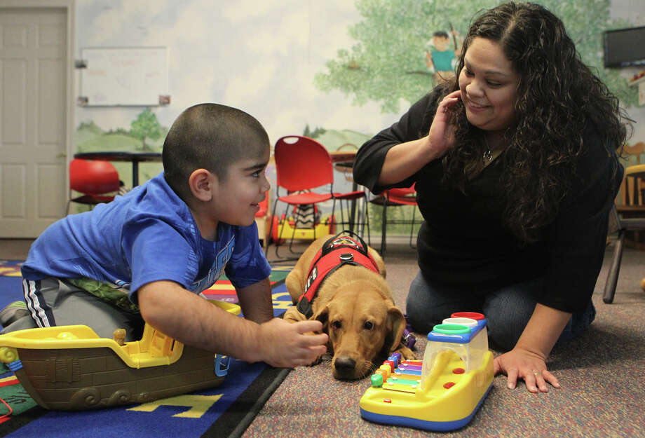 Four-year-old John Carlos Lopez plays with mom Elvia Lopez at Any Baby Can. Grace the dog can monitor the boy's blood sugar level and can alert when necessary. Photo: John Davenport, San Antonio Express-News / ©San Antonio Express-News/Photo Can Be Sold to the Public