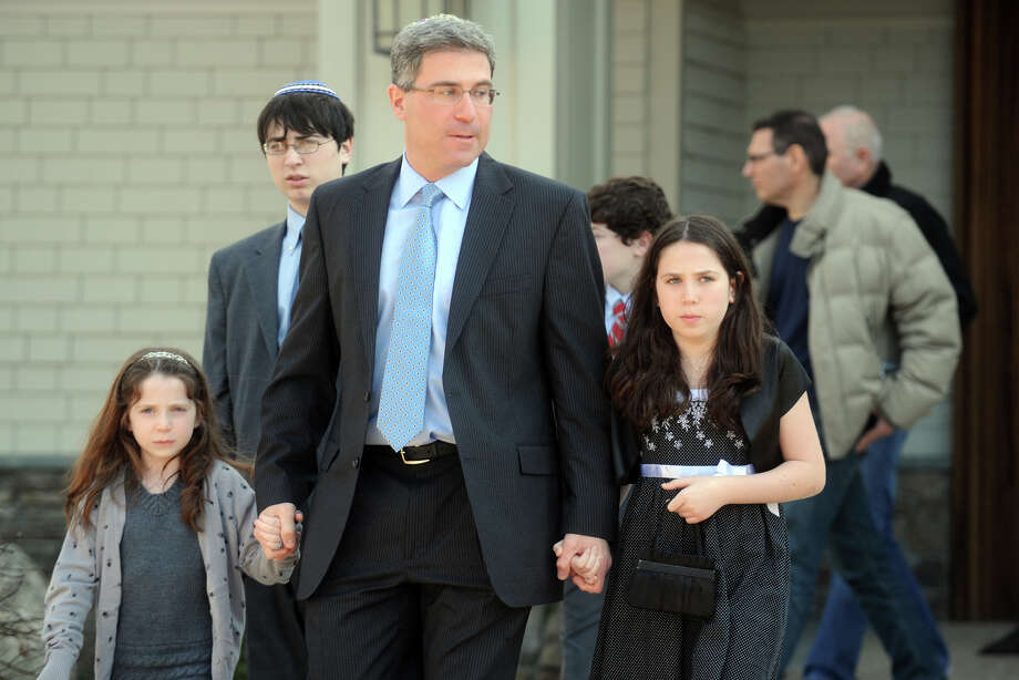 A family leaves Adath Israel following a Saturday prayer service in Newtown, Conn. Dec. 15th, 2012, the day after the mass shooting at Sandy Hook Elementary School where 27 people were killed. Photo: Ned Gerard / Connecticut Post