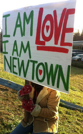 "A Newtown woman, who declined to give her name, sat near the entrance to Interstate 84, holding a sign that read "" I am love, I am Newtown."" She said she was holding a vigil of love. ""It's devastating,"" she said. ""There are no words. I'm overwhelmed with this place being known as a place of darkness."" Photo: Amanda Cuda, Hearst Connecticut Newspapers/Am / Connecticut Post"