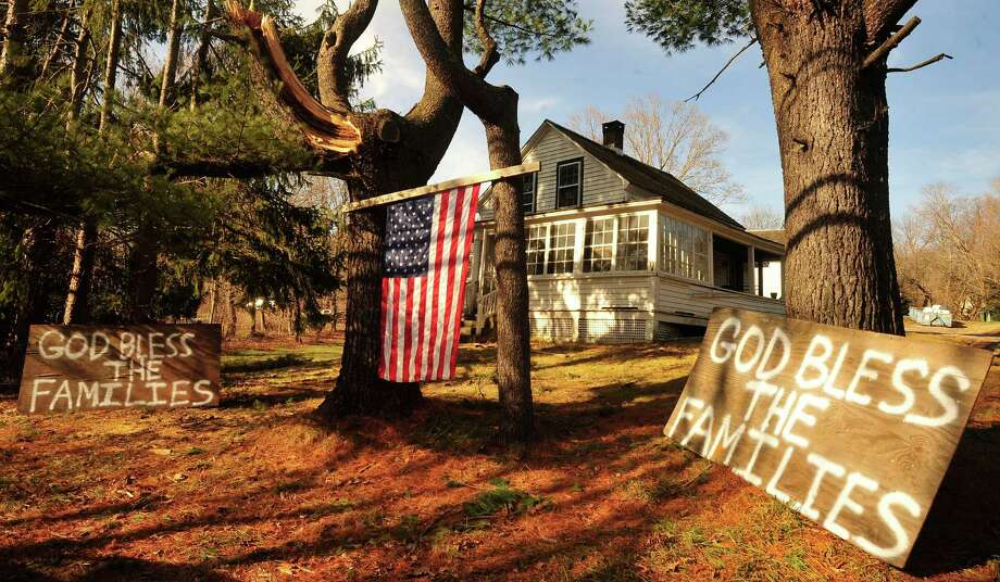 Signs in front of a house near the site of the mass shooting at Sandy Hook Elementary School express neighborhood feelings in Newtown Saturday Dec. 15, 2012. Photo: Michael Duffy