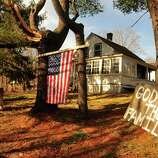 Signs in front of a house near the site of the mass shooting at Sandy Hook Elementary School express neighborhood feelings in Newtown Saturday Dec. 15, 2012.