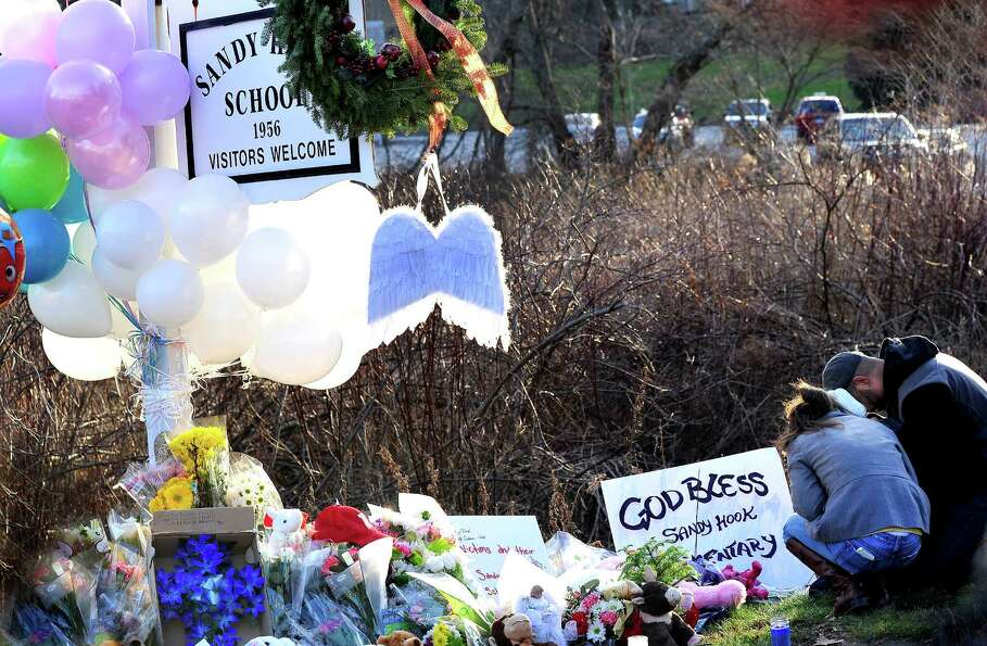 Mourners place flowers on a memorial built around the sign for the Sandy Hook School in Newtown Satu