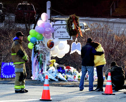 Mourners react after placeing flowers on a memorial built around the sign for the Sandy Hook School in Newtown Saturday, Dec. 15, 2012. Sandy Hook Elementary School was the site of a mass shooting on Friday. Photo: Michael Duffy